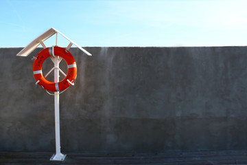 lifebuoy on a concrete wall background