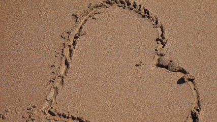 Heart drawn on the beach sand with sea wave