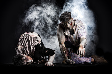 Two male zombies crawling on their knees, on dark background