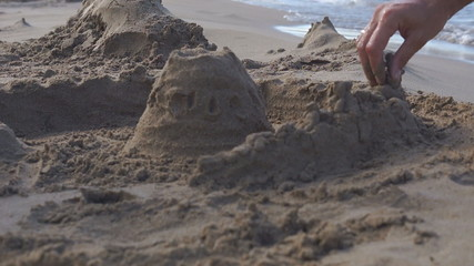 Builds sand castle on the beach.