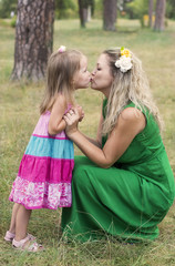 Daughter kissing her mother in a park