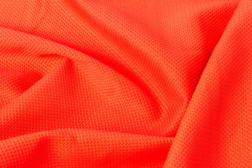 texture of bright, acid orange cloth with pleats