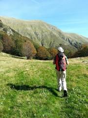 Escursista cammina su di un prato alle pendici di un monte