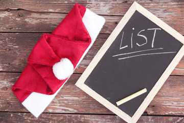 Santa claus hat and chalkboard on a wooden background