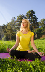 Beautiful blonde meditating in nature. sun rays