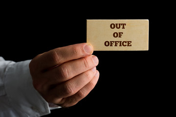 Man with a business card reading - Out of Office