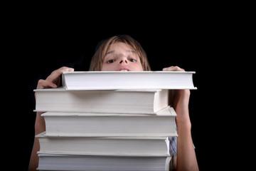 Enfant regardant derrière une pile de livres blanc