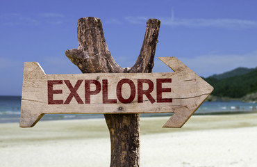 Explore wooden sign with a beach on background