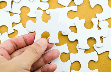Jigsaw puzzle in hand on recycle paper background
