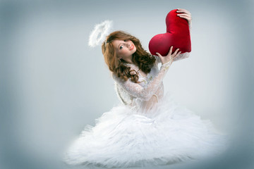 Girl dressed as angel posing with teddy heart