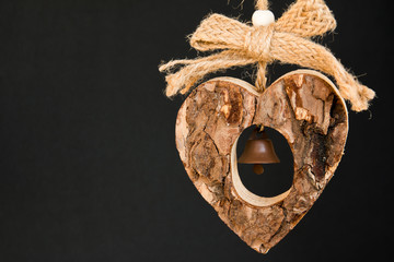 Bark wooden heart on a rope with little opaque brass bell in the
