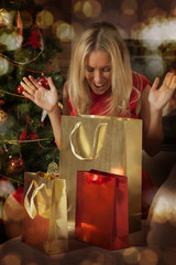 Young woman opening Christmas presents