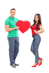 Young couple holding a big red heart