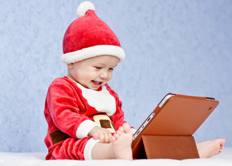 happy santa helper baby boy with digital tablet