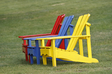 colorful Adirondack chairs on a green lawn
