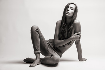 Fashion model sitting on a floor in a jeans