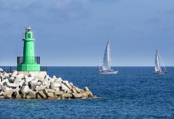 barche a vela costeggiano il faro