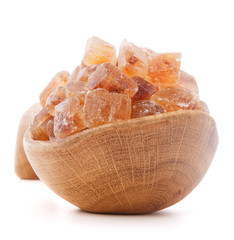 Brown cane caramelized lump sugar in wooden bowl isolated on whi