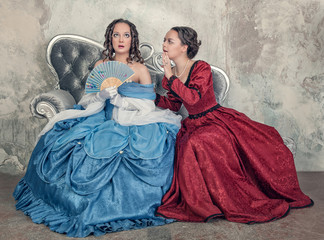 Two beautiful women in medieval dresses gossip on the sofa