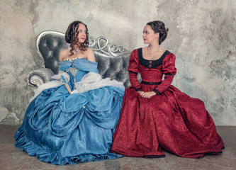 Two beautiful women in medieval dresses on the sofa