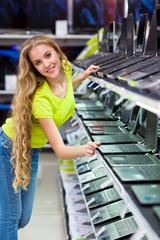 девушка выбирает ноутбук в магазине