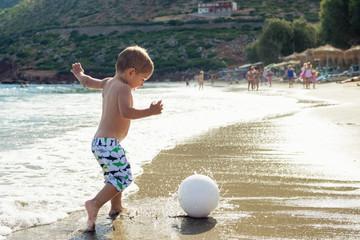 Ребенок играет в мяч на пляже.