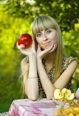 Девушка сидит за столом в саду, с яблоком в руках