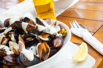 Plate full of mussels with garlic sauce on table