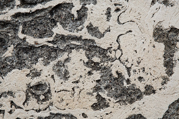 Plastered gray stone surface with cracks
