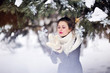 winter girl blowing on a snowflake in knitted mittens