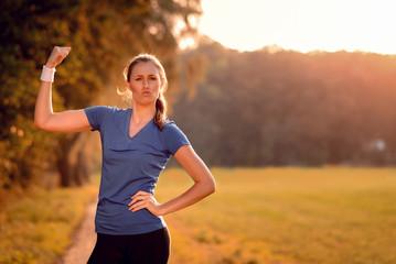 Ausdrucksstarke junge Frau pumpt ihren Arm