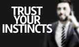 Business man with the text Trust your Instincts poster