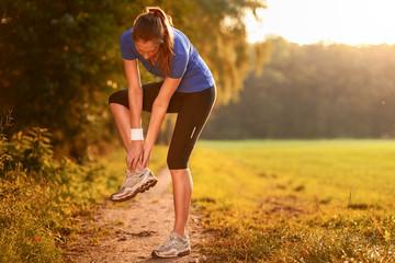 Junge Frau beim Training fasst sich ans Sprunggelenk