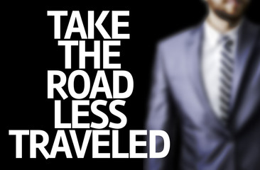 usiness man with the text Take the Road Less Traveled