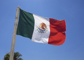 Mexican flag on blue sky.