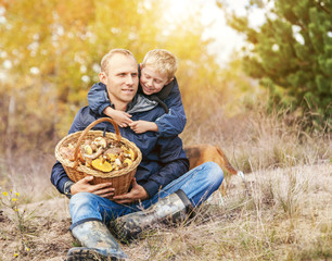 Father with son rest in autumn forest