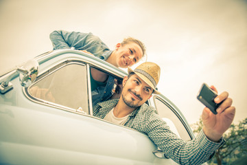 Happy couple travelling on a vintage car