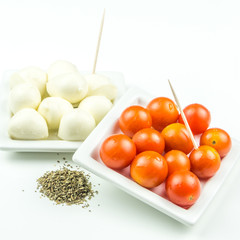 cherry tomatos, mozarella and ground basil with toothpicks on wh