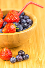 strawberries and blueberries in wooden cup with straw