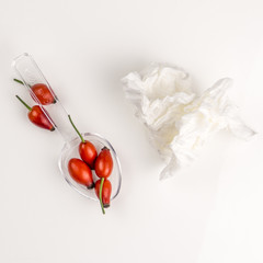 Rose hip on a medicine spoon with used handkerchief tissue