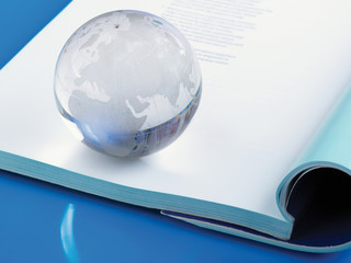 glass globe lying on book.