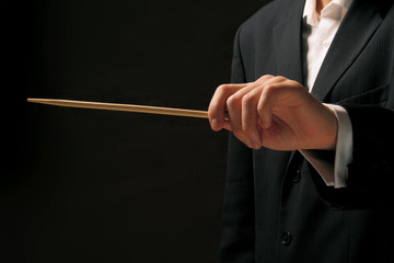 Concert conductor's hands with a baton isolated on a black