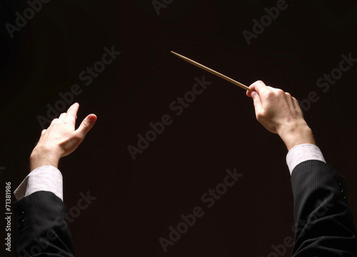 Leinwanddruck Bild Concert conductor's hands with a baton isolated on a black