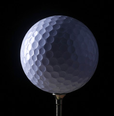 A close-up of a golf ball over dark background