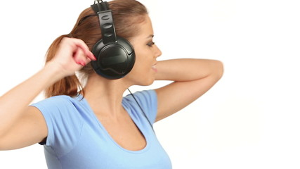 Beautiful lady listening music on large headphones, looking at c