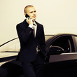 Young business man calling on the cell phone at the car