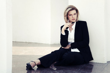 Young business woman with a mobile phone sitting at the wall