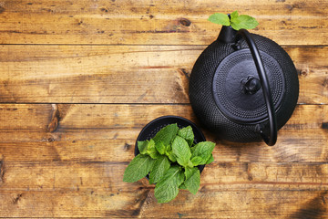 Chinese traditional teapot with mint leaves on wooden