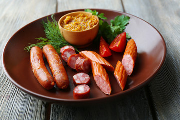 Assortment of tasty thin sausages on plate on wooden background