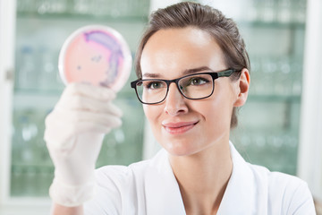 Worker of laboratory watching Petri dish